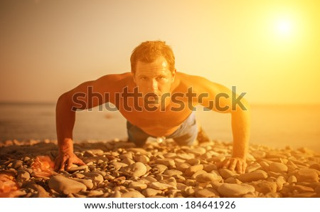 man athlete trains, practicing, playing sports pushed on the nature on the beach - stock photo