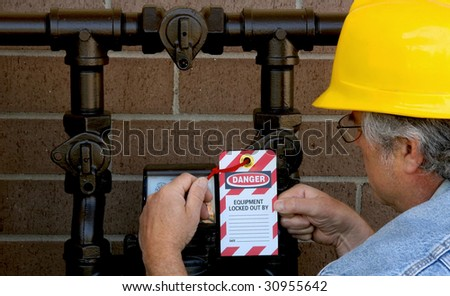 man attaching lockout tag to gas meter - stock photo