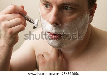 Man attempting to get a close shave with his razor  - stock photo