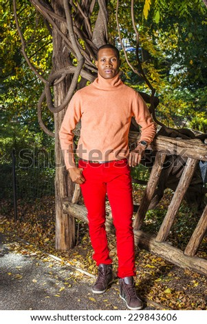 Man Autumn Casual Fashion. Dressing in light orange sweater with high collar, red pants, patterned boot shoes, wearing wristwatch, a young black guy is standing by wooden fence, looking at you
