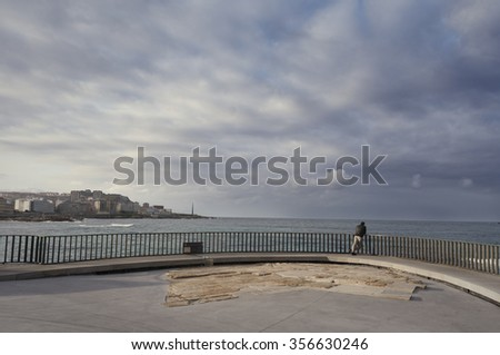 Man back leaning against the railing enjoying the solitude and calm sea - stock photo