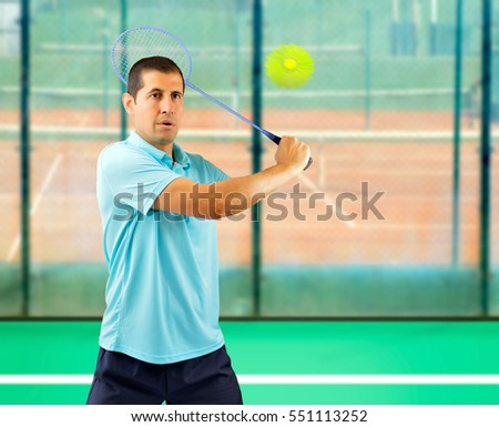 man badminton player standing and swatting the ball