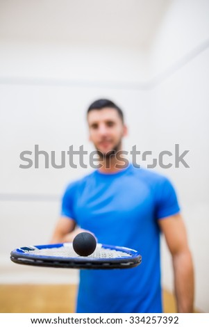 Man balancing a ball on his racket in the squash court - stock photo