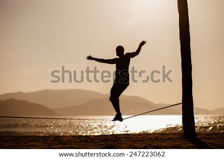 man balancing on slackline with sea view silhouette - stock photo