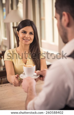 Man barista giving cup of coffe to woman at counter in the coffee shop. - stock photo