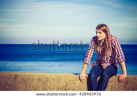 Man bearded long hair wearing plaid shirt casual style relaxing by seaside at summer sunny windy day