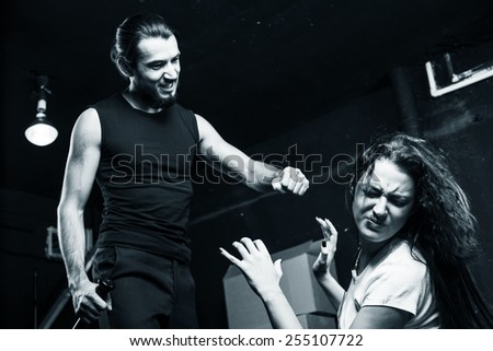 Man beating up his wife on black-and-white background - stock photo