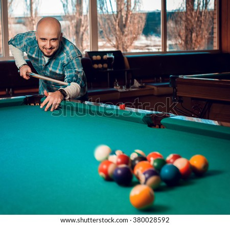 man begins to play a game of billiards and breaks pyramid of balls on the table. American pool billiard. Pool billiard game. Billiard sport concept. - stock photo