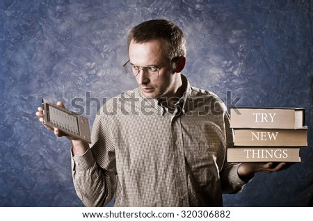 Man being focused on light and handy ebook reader, holding heavy books in other hand, try new things written on books