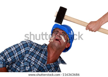 Man being hit over the head by hammer - stock photo
