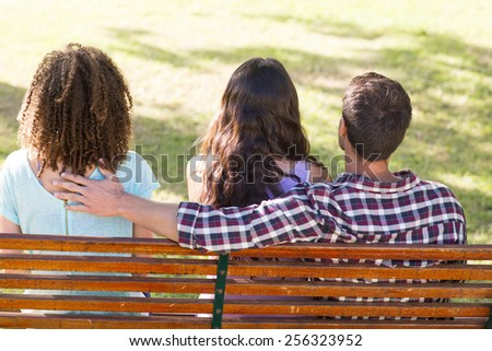 Man being unfaithful in the park on a sunny day - stock photo
