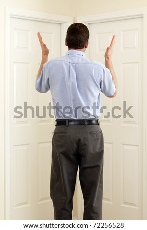 Man between two doors with hands in the air not sure which to choose. - stock photo
