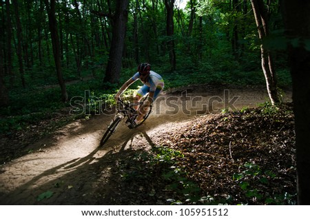 Man bikes in the green forest - stock photo
