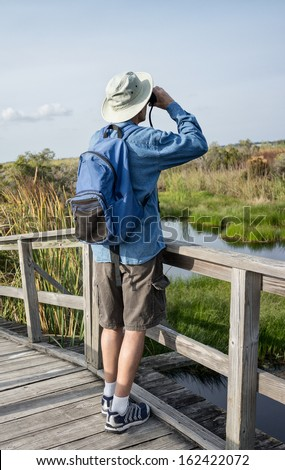 Man Birdwatching in Florida Wetlands on Weathered Wooden Foot Bridge