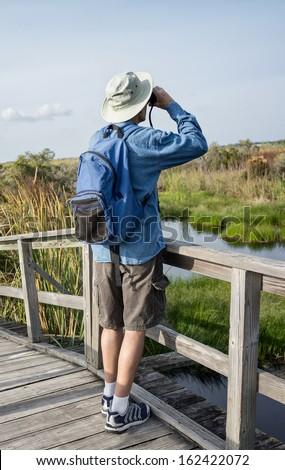 Man Birdwatching in Florida Wetlands on Weathered Wooden Foot Bridge - stock photo