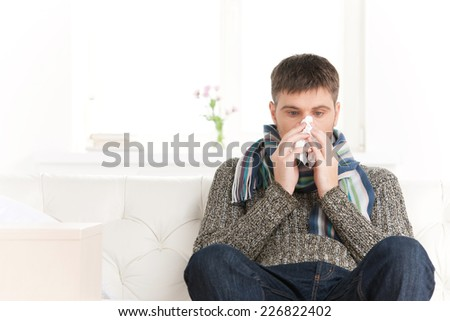 Man blowing his nose in his living room. guy sitting on sofa and feeling sick - stock photo