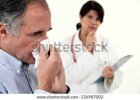 Man blowing his nose next to a doctor - stock photo