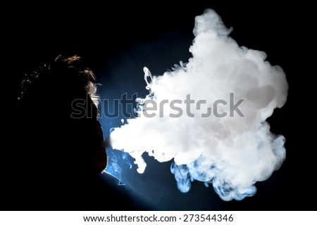 Man blowing vapor cloud from an E-Cigarette - stock photo