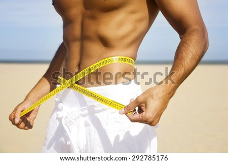 Man body on the beach with centimeter - stock photo