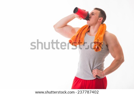 Man bodybuilder posing on white background Man is holding a shaker for drinks. Man drinking a protein shake, water, amino acids from the shaker. Sports, sports nutrition, food additive. - stock photo