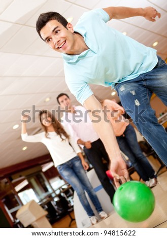 Man bowling and his friends cheering at the background - stock photo