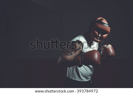Man boxer on a dark background. Sport, man, boxing, training, fighter, warrior, fighting without rules. black and white