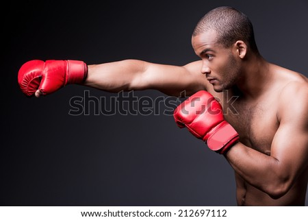 Man boxing. Side view of young shirtless African man in boxing gloves exercising while standing against grey background - stock photo