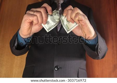 Man breaks hundred dollar bill. - stock photo