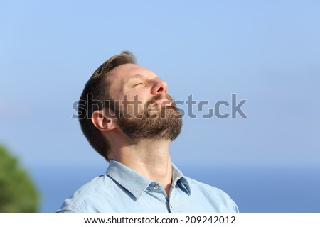 Man breathing deep fresh air outdoors with a blue sky in the background          - stock photo