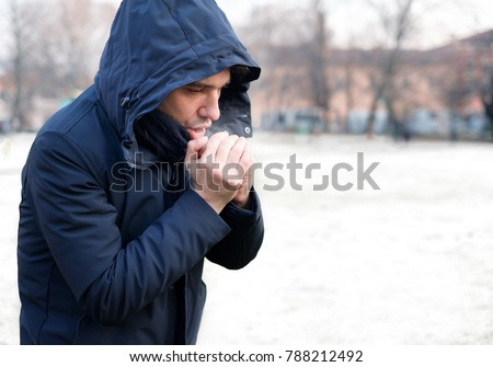 Man breathing on his hands to keep them warm