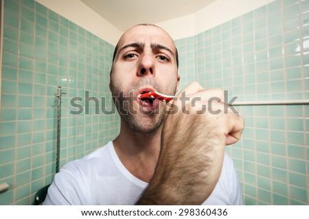 Man brushing his teeth - stock photo