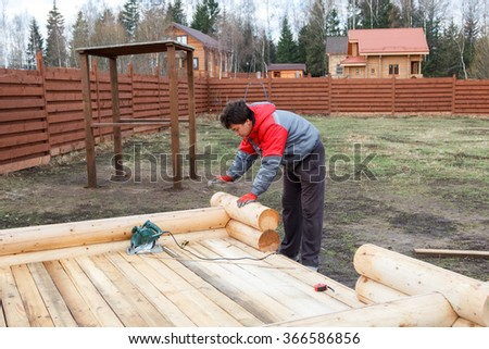 man builds a structure made of logs - stock photo