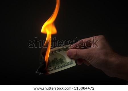 man burns money on black background - stock photo