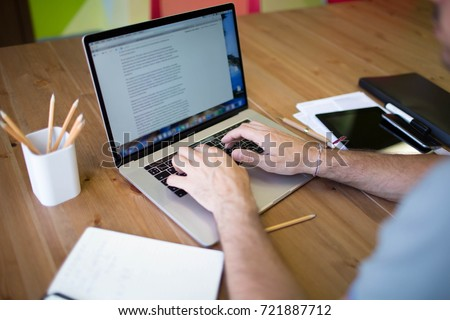 Man business planning expert working on laptop computer. Male content writer for financial  presentation using modern notebook. Hipster guy skilled e-book writer using net-book, sitting at desktop