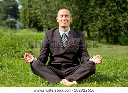 Man businessman meditating outdoors in lotus pose - stock photo