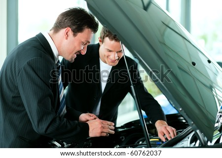 Man buying a car in dealership looking under the hood at the engine - stock photo