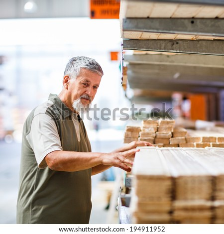 Man buying construction wood in a  DIY store for his DIY home re-modeling project - stock photo