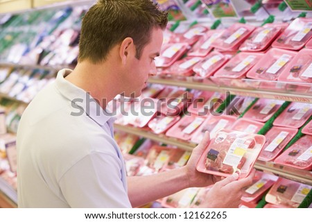 Man buying fresh meat from supermarket - stock photo