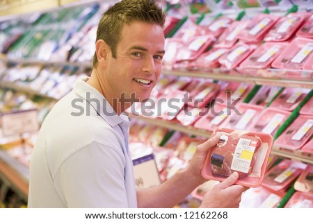 Man buying fresh meat from supermarket counter - stock photo
