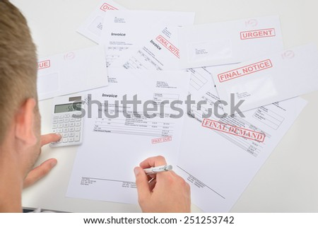 Man Calculating Financial Bills And Bank Statements - stock photo