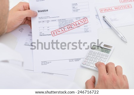 Man Calculating Invoice With Final Demand Notification - stock photo
