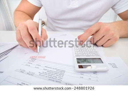 Man Calculating Past Due Statement Using Calculator - stock photo