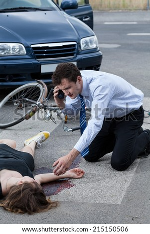 Man calling an ambulance for injured woman after road accident - stock photo