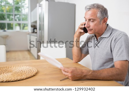 Man calling and reading a sheet of paper on the table - stock photo