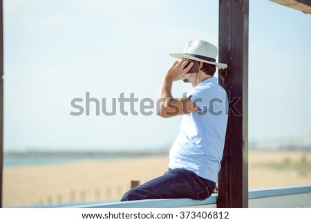 Man calling by cell phone on the beach wooden terrace background - stock photo