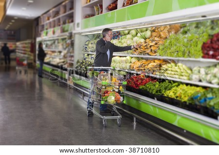 Man calling by cellular phone while picking vegetables in a supermarket. All recognizable logos and brands have been retouched or blurred out. - stock photo