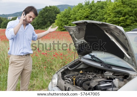 man calling the repair service after car breakdown - stock photo