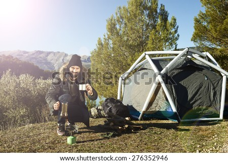 Man camping drinking coffee near tent smiling happy outdoors in mountain forest enjoying sun looking at camera. Happy bearded male relaxing after outdoor activity hiking. Travel Caucasian man. - stock photo