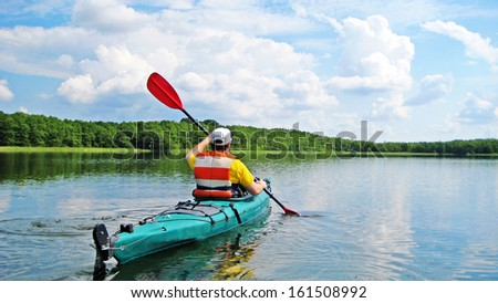 man canoeing on a lake - stock photo