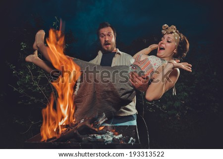 Man carried his wife in his arms, and going to burn her at the stake  - stock photo
